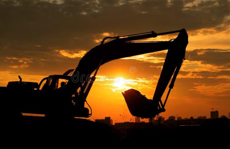 Zonsondergang en Graafwerktuig stock fotografie