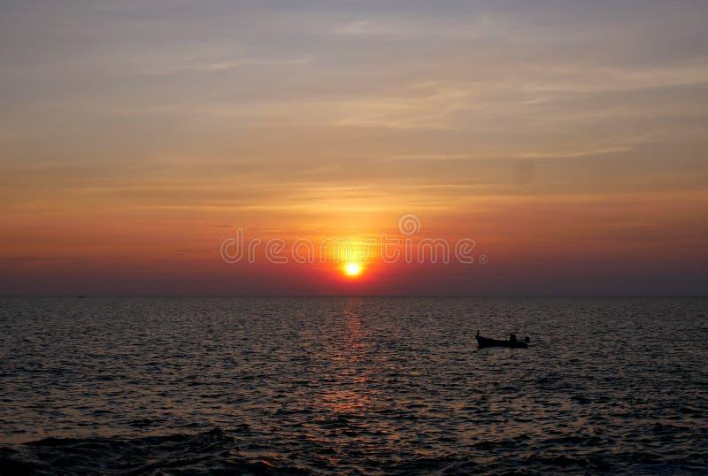Zonsondergang en kleine boten in het overzees royalty-vrije stock afbeelding