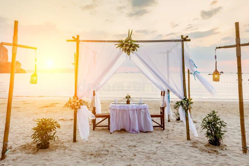 Zonsondergang en romantisch luxediner bij tropisch strand Verfraaide lijst met wijnstokglazen Witte en magenta tonen royalty-vrije stock afbeeldingen