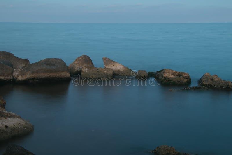 Zonsondergang en rots op het overzees stock foto's