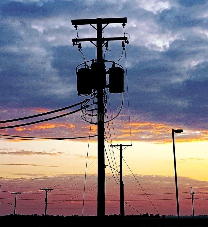 Zonsondergang en telefoonpolen stock fotografie