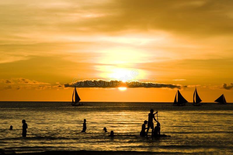 Zonsondergang en varende boten op wit strand royalty-vrije stock fotografie