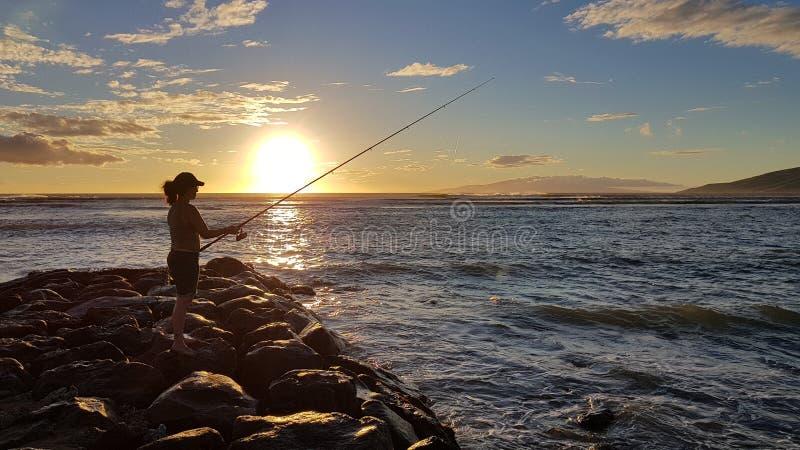 Zonsondergang en visser stock foto's