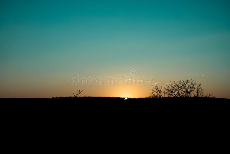 Zonsondergang en vliegtuiglijnen op hemel royalty-vrije stock afbeelding
