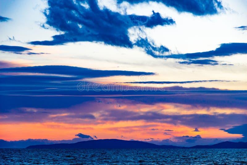 Zonsondergang in Follonica in de recente winter met cloudscape en schaduwen van rood royalty-vrije stock afbeelding