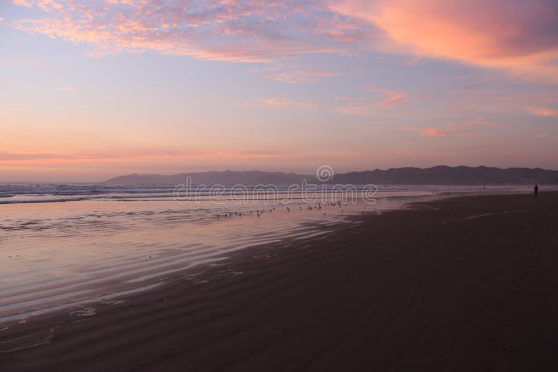 Zonsondergang, golven en waadvogels bij Pismo-Strand royalty-vrije stock afbeeldingen