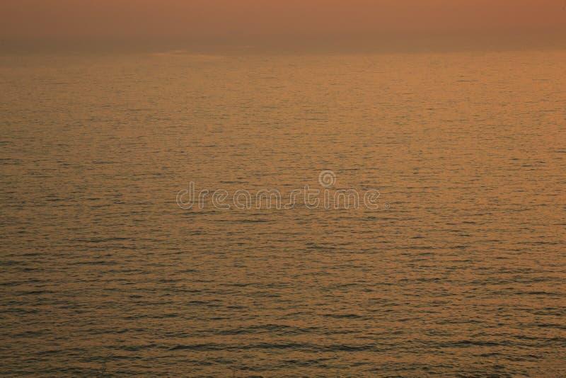 Zonsondergang gouden lichte bezinning over van de overzeese de oppervlakteachtergrond golfrimpeling De samenvatting, kalmte, reis stock foto