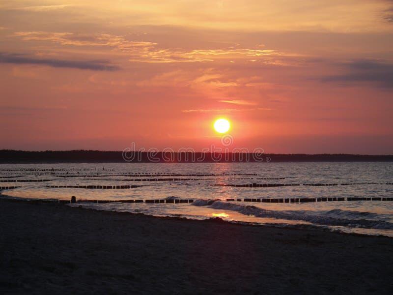 Zonsondergang heldere hemel over water bij de Oostzee, Estland stock foto's