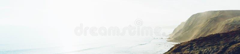 Zonsondergang in het berg natuurlijke landschap Groene vallei op dramatische hemel als achtergrond, mistige overzeese oceaan Pers stock afbeelding