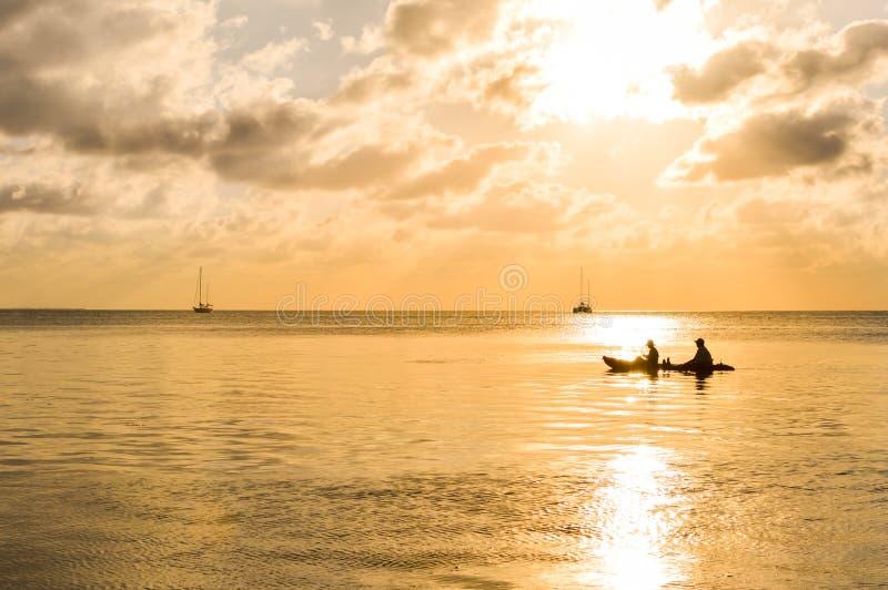 Zonsondergang in het Caraïbische overzees door Caye Breeuwijzereiland, Belize stock afbeelding