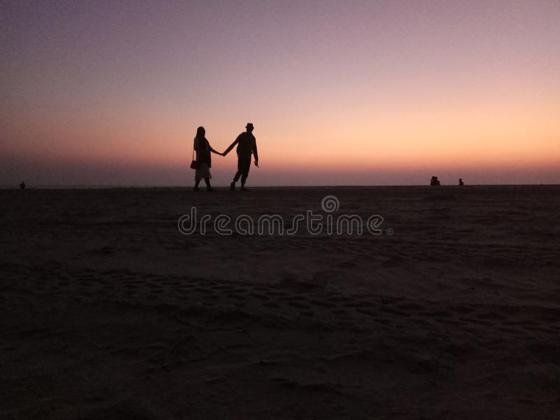 Zonsondergang -1 het houden van paar het lopen stock foto