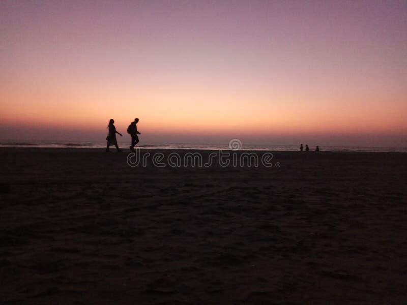 Zonsondergang -1 het houden van paar het lopen royalty-vrije stock afbeelding
