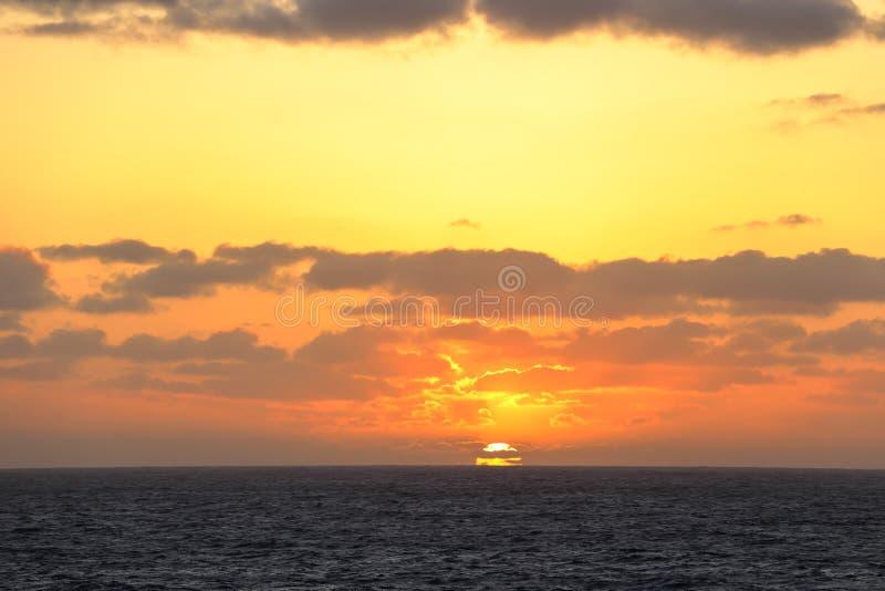 Zonsondergang in het midden van de vreedzame oceaan stock foto's
