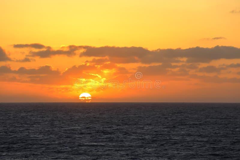 Zonsondergang in het midden van de vreedzame oceaan royalty-vrije stock afbeelding