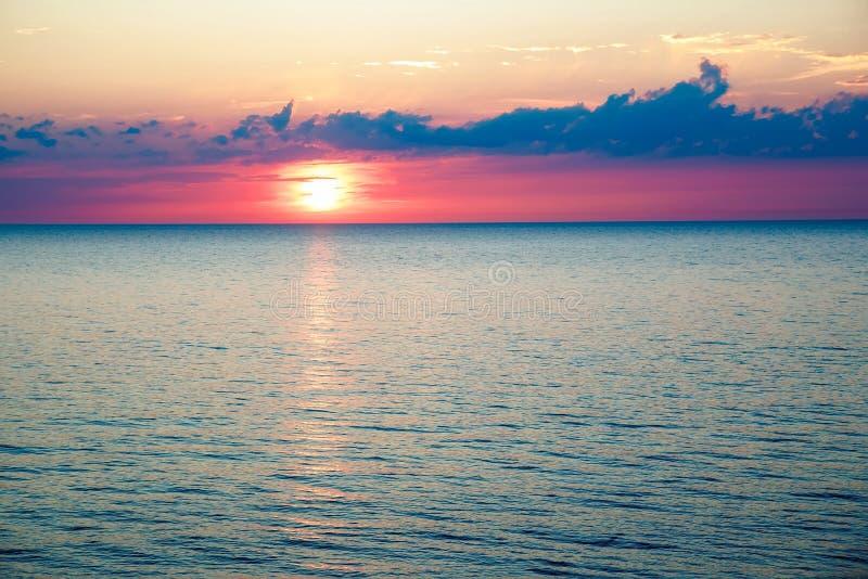 Zonsondergang in het overzees en mooie cloudscape stock fotografie
