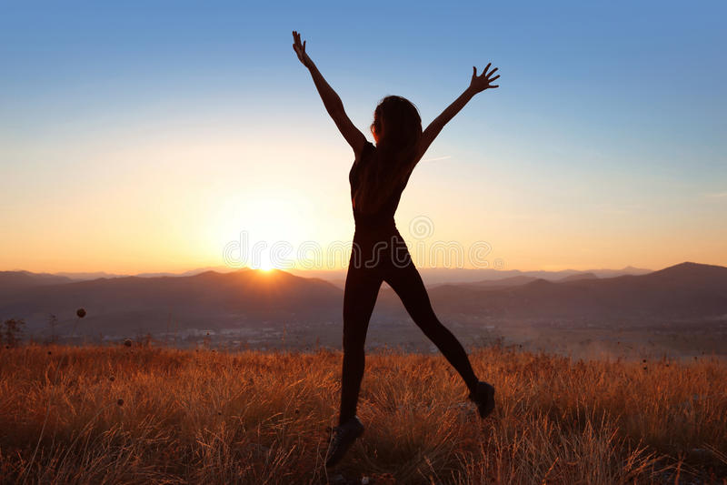 Zonsondergang Het vrije vrouwensilhouet springende genieten in openlucht van in een whe stock afbeeldingen