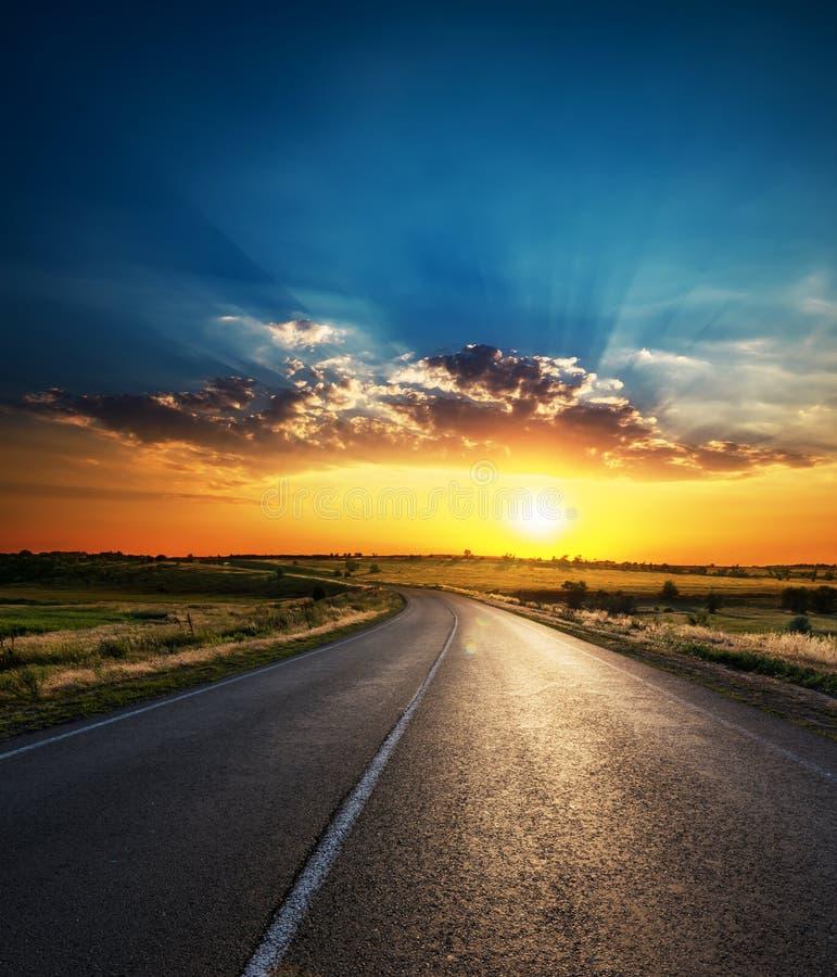 Zonsondergang in lage dramatische wolken over asfaltweg royalty-vrije stock foto's