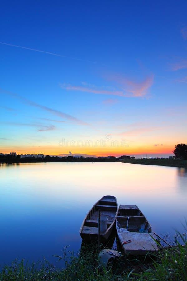 Zonsondergang langs de vijver met twee boten royalty-vrije stock afbeelding
