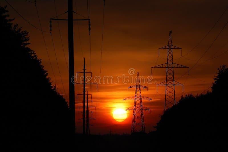 Zonsondergang in lijn met hoog voltage royalty-vrije stock afbeeldingen