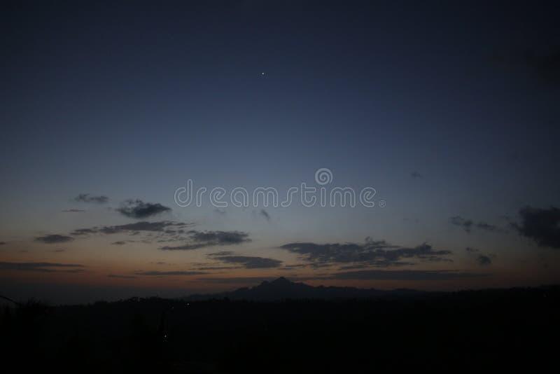 Zonsondergang met Bergen stock foto's