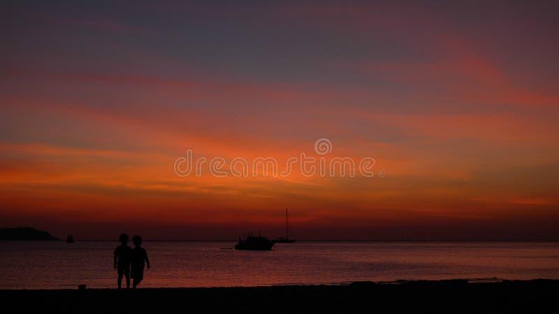 Zonsondergang met de silhouetten die van de twee kinderen bij de kust spelen royalty-vrije stock foto's