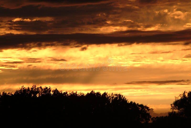Zonsondergang met donkere wolken stock afbeeldingen