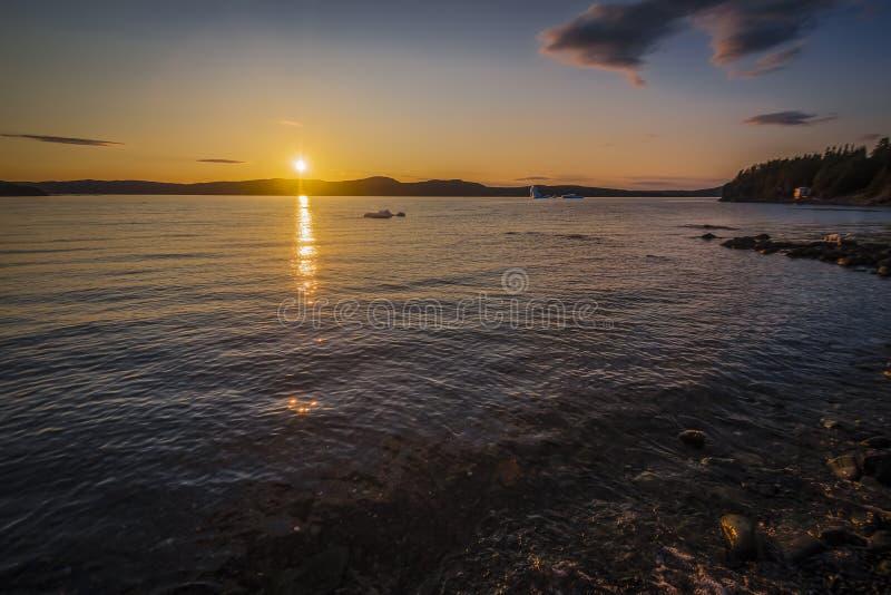 Zonsondergang met een Ijs Berg in mening langs een kustgebied royalty-vrije stock fotografie