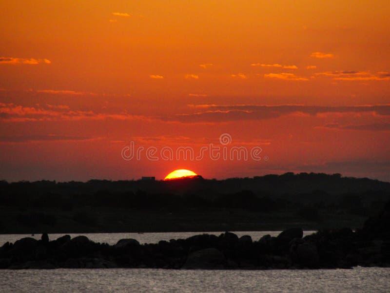Zonsondergang met een oranjerode en gele hemel in een overzees van het rivier oceaanmeer stock afbeelding