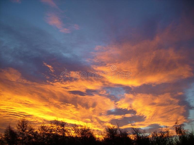 Zonsondergang met gouden vurige wolken op de zomer stock afbeelding
