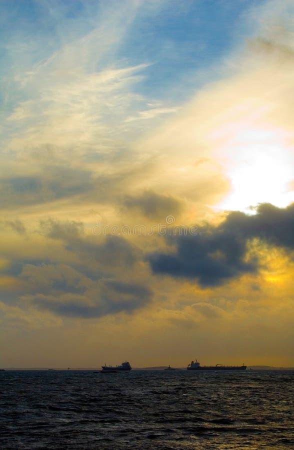 Zonsondergang met schepen op de horizon stock foto's