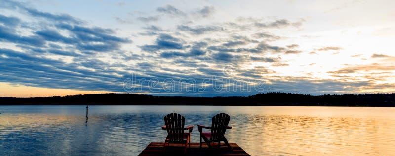Zonsondergang met stoelen op een meer stock foto's