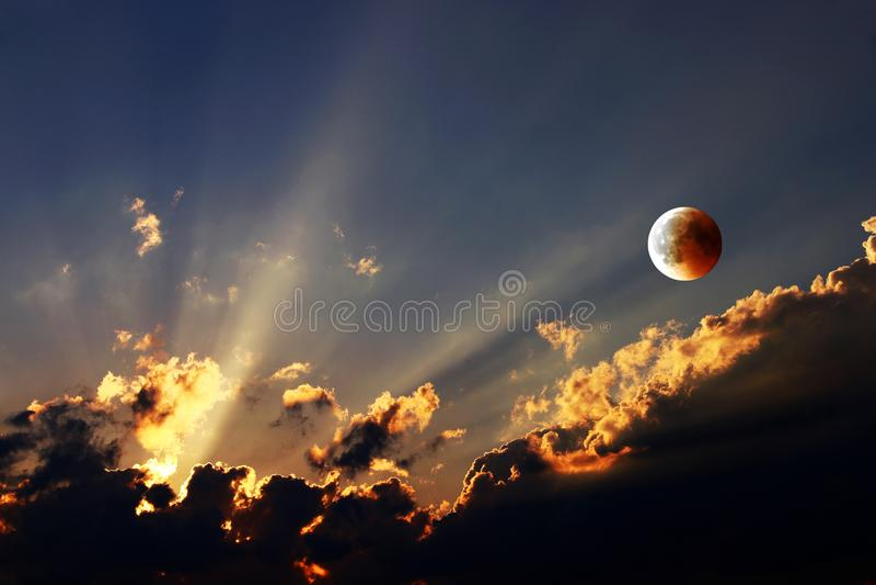 Zonsondergang met stralen van lichte en het toenemen maan met maanverduistering in de avond hemel stock afbeeldingen