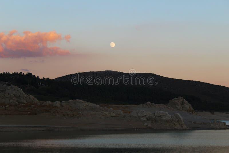 Zonsondergang met volle maan over meer stock afbeelding
