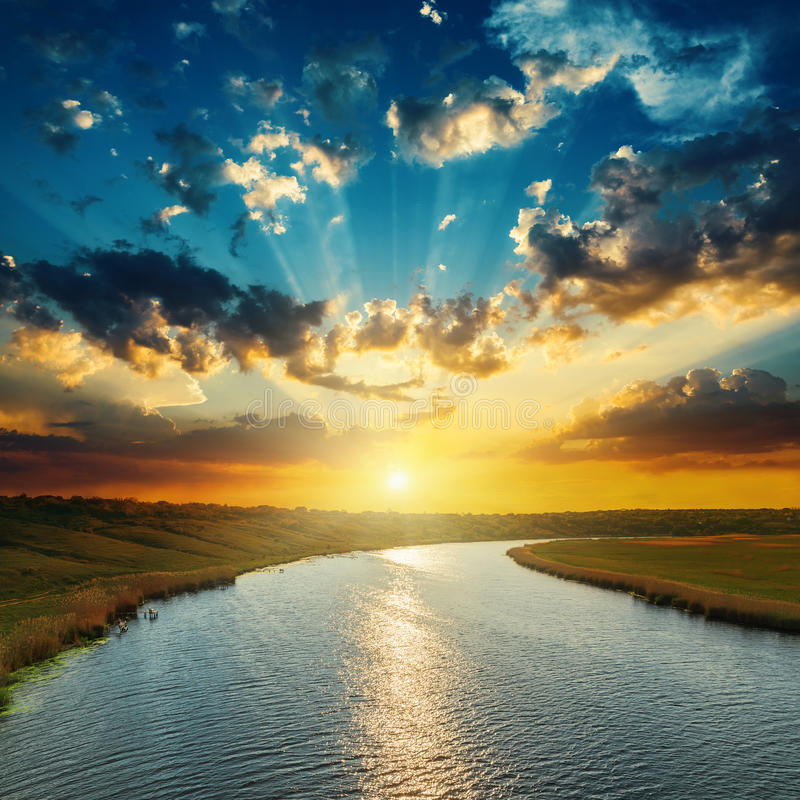 Zonsondergang met wolken, lichte stralen over rivier stock afbeelding