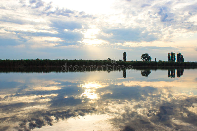 Zonsondergang met wolken, lichte stralen over rivier met bezinningen royalty-vrije stock fotografie