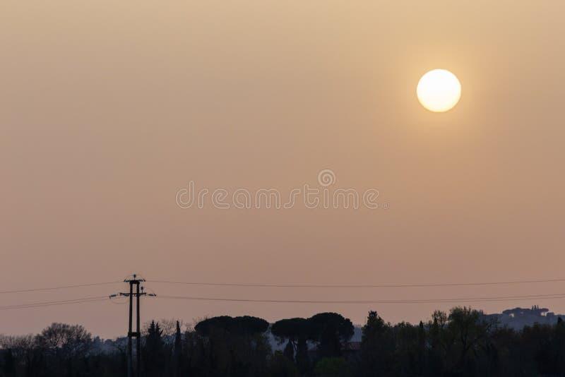 Zonsondergang met zand in de atmosfeer wordt opgeschort, die het hemelrood, over sommige bomensilhouetten en machtslijnen die col royalty-vrije stock foto's