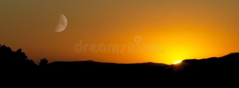 Zonsondergang met zon en maan royalty-vrije stock foto's