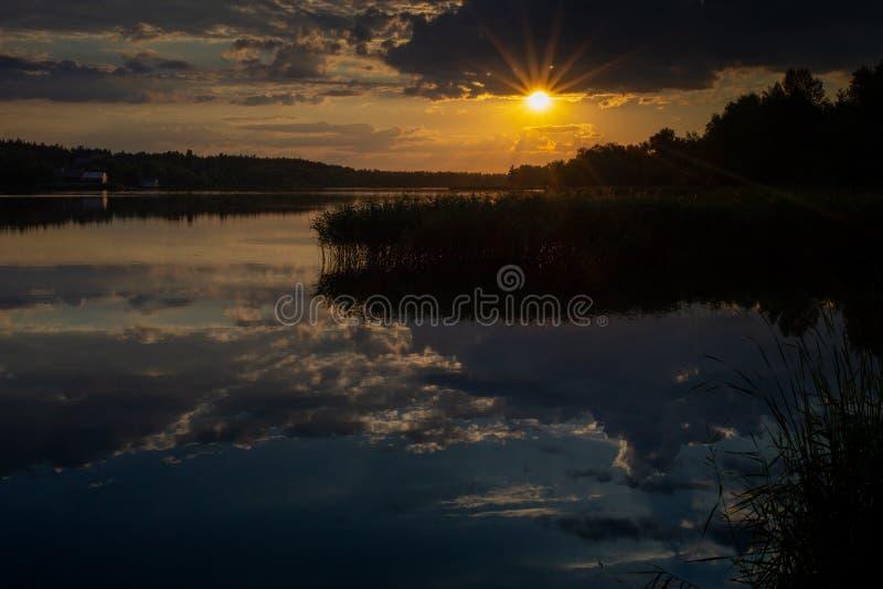 Zonsondergang met zonstralen bij de rivier Grote bezinning in water met rietinstallatie stock fotografie