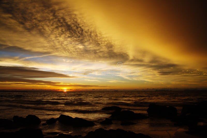 Zonsondergang na zware regen met de onweerswolken en de stenen van de arcusplank in de oceaan op tropisch eiland Ko Lanta, Thaila royalty-vrije stock foto's