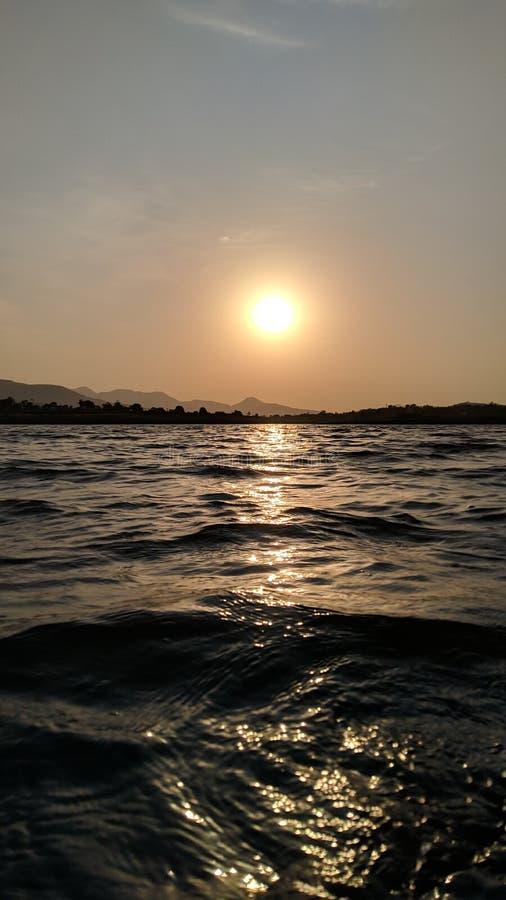 Zonsondergang naast rivier stock afbeeldingen