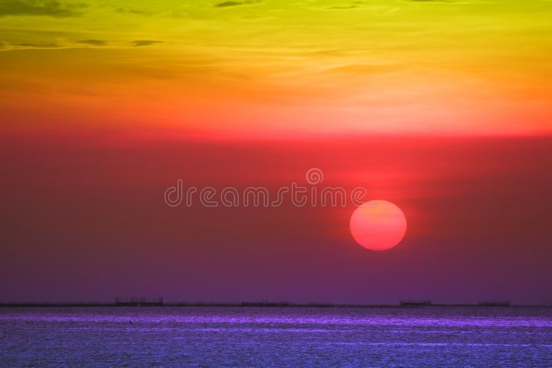 zonsondergang op achter de avondwolk van de regenbooghemel over schemering die op overzees vissen royalty-vrije stock afbeelding