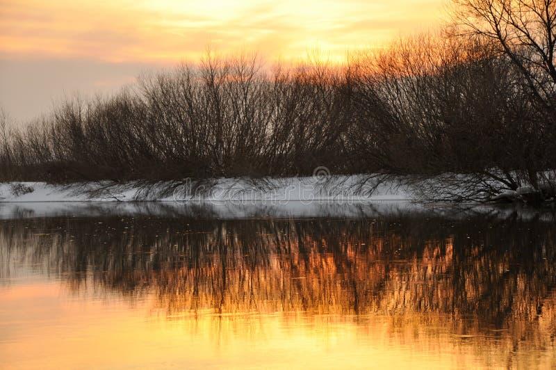 Zonsondergang op de de winterrivier stock afbeelding