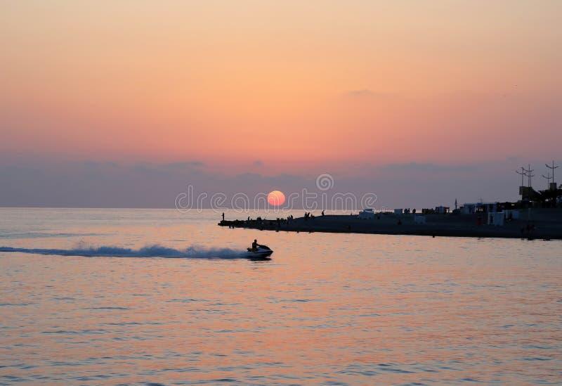 Zonsondergang op de kust met een rust mensen stock foto's