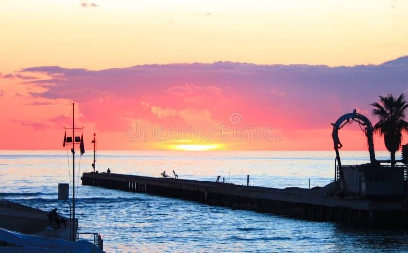 Zonsondergang op de overzeese mening van de haven kleine die haven in levendige en heldere oranje en roze kleuren van zonsonderga royalty-vrije stock foto