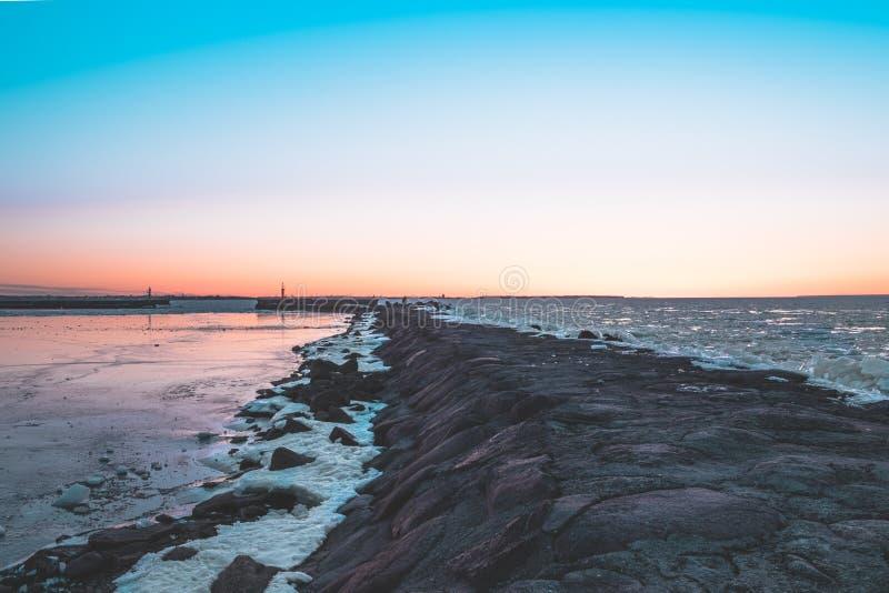 Zonsondergang op de pijler door de bevroren Oostzee stock foto