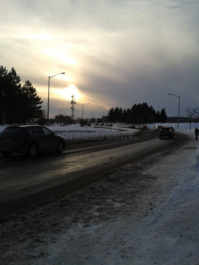 Zonsondergang op de weg met auto's het overgaan stock afbeelding