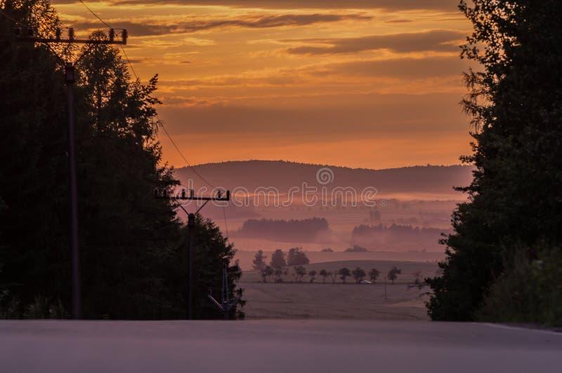 Zonsondergang op een landweg stock foto's