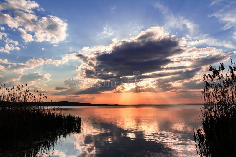 Zonsondergang op een meer, landschap Mooie aard Blauwe hemel en wolken royalty-vrije stock afbeelding