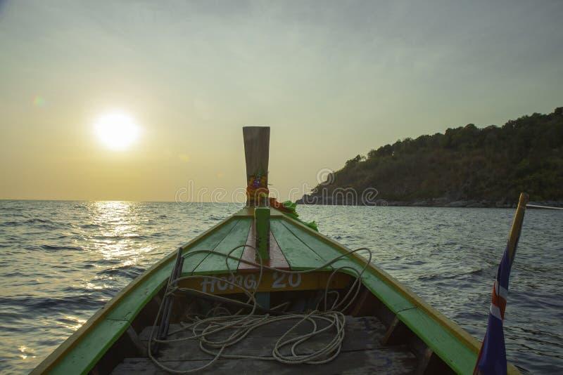Zonsondergang op een overzees Een deel van exotische boot met bloemslinger en amulet Overzeese reis Zeegezicht met golven en kust royalty-vrije stock foto's