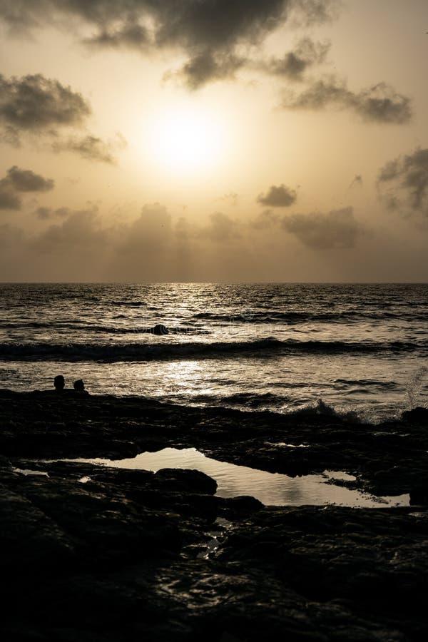 Zonsondergang op een rotsachtig strand royalty-vrije stock fotografie